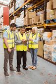Manager writing on clipboard talking to colleague in a large warehouse