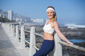 Fit blonde standing on the pier on a sunny day