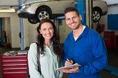 Mechanic smiling at the camera with customer at the repair garage