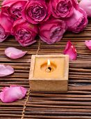 Candle in wooden bowl and rose with Petals on mat, Valentines Day background,