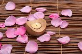 rose Petals and candle in wooden bowl on mat