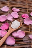 Rose petals with white salt in wooden bowl on mats