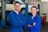 Team of mechanics smiling at camera at the repair garage