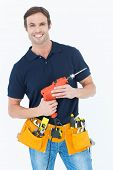 Portrait of confident carpenter holding portable drill machine over white background