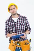 Thoughtful male repairman writing on clipboard over white background