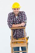 Portrait of happy repairman holding spanner while climbing ladder on white background