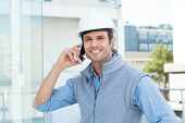 Portrait of smiling male architect using mobile phone outdoors
