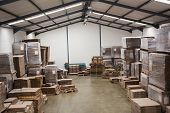 Many stack of cardboard boxes in a large warehouse