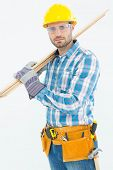 Portrait of confident construction worker carrying wooden planks against white background