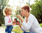 Happy Mother And Her Daughter Blowing Soap Bubbles On A Warm Summer Day