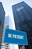 The word be patient and blue billboard against low angle view of skyscrapers