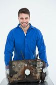 Portrait of smiling young male machanic carrying old car engine on white background