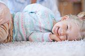 Joyful kid in casualwear lying on the floor