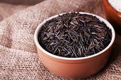 Black rice in bowl on sackcloth background