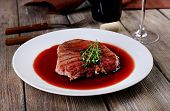 Grilled steak in wine sauce on plate on table close up