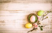 Colorful easter eggs and branch with spring flowers. Vintage style
