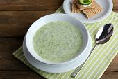 Cucumber soup in bowl on rustic wooden table background