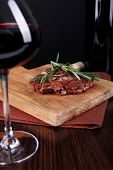 Glass of wine with grilled steak on wooden background