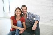 Trendy couple sitting on house floor
