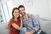 Cheerful young couple relaxing in sofa at home
