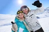 Cheerful couple having fun at top of ski slope
