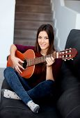 Pretty girl playing guitar on the couch at home