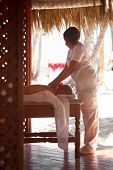 pic of therapist  - Massage therapist working in gazebo on the beach. Massage services on resort