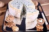 Blue cheese with nuts on metal tray and wooden table background