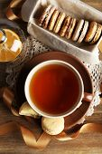 Colorful macaroons with cup of tea on wooden background