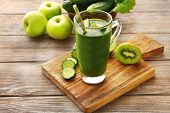 picture of fruit-juice  - Green fresh healthy juice with fruits and vegetables on cutting board and wooden table background - JPG