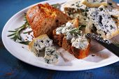 Blue cheese with sprigs of rosemary, bread and nuts on plate and color wooden table background
