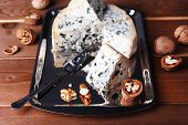 Blue cheese with nuts and blade on metal tray and wooden table background