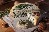 Blue cheese with sprigs of rosemary and nuts on board with sheet of paper and wooden table background