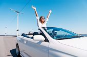 picture of road trip  - Happy young couple enjoying road trip in their convertible while woman raising arms and smiling - JPG