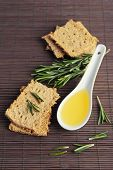 Crispbread with sprigs of rosemary and spoon of oil on bamboo mat background