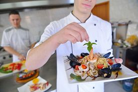 pic of school fish  - Handsome chef dressed in white uniform decorating pasta salad and seafood fish in modern kitchen - JPG