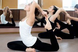 foto of slim model  - Girls doing yoga exercises in class sitting in asana eka pada radzhakapotasana (One-Legged King Pigeon Pose) - hands grasps feet instructor on the background coaching one of the yoga students ** Note: Visible grain at 100%, best at smaller sizes - JPG