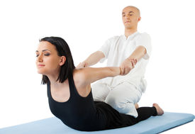 image of thai massage  - Young female receiving massage by therapist in traditional thai position - JPG