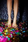 picture of barefoot  - Barefoot female standing on the floor with confetti - JPG