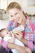 picture of feeding  - Young Mother With Baby Feeding On Sofa At Home - JPG