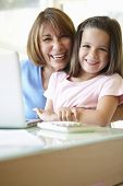 stock photo of grandmother  - Hispanic Grandmother Using Laptop And Calculator With Granddaughter - JPG