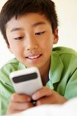foto of pre-teen boy  - Young boy using smartphone - JPG