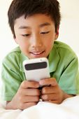 pic of pre-teen boy  - Young boy using smartphone - JPG