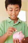 picture of pre-teen boy  - Young boy putting money in piggybank - JPG