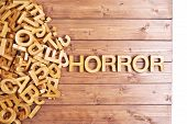 image of horror  - Word horror made with block wooden letters next to a pile of other letters over the wooden board surface composition - JPG