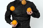 stock photo of juggling  - Man in black shirt juggling with four oranges - JPG