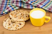 pic of shortbread  - Two shortbreads rings with peanuts and cup of milk on wooden bamboo table - JPG
