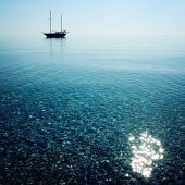 picture of sail ship  - Morning sea with boat on the horizon. Aged photo. Sailing ship profile. Toned image. Sunbeams on the sea surface. Calm Sea with a Sailing Vessel. Cirali Antalya Province Turkey.