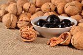 image of walnut  - Jam from walnuts on a saucer and walnuts on a sacking background - JPG