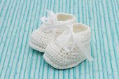 stock photo of booty  - Retro Baby Booties White Baby Booties on a grunge background - JPG
